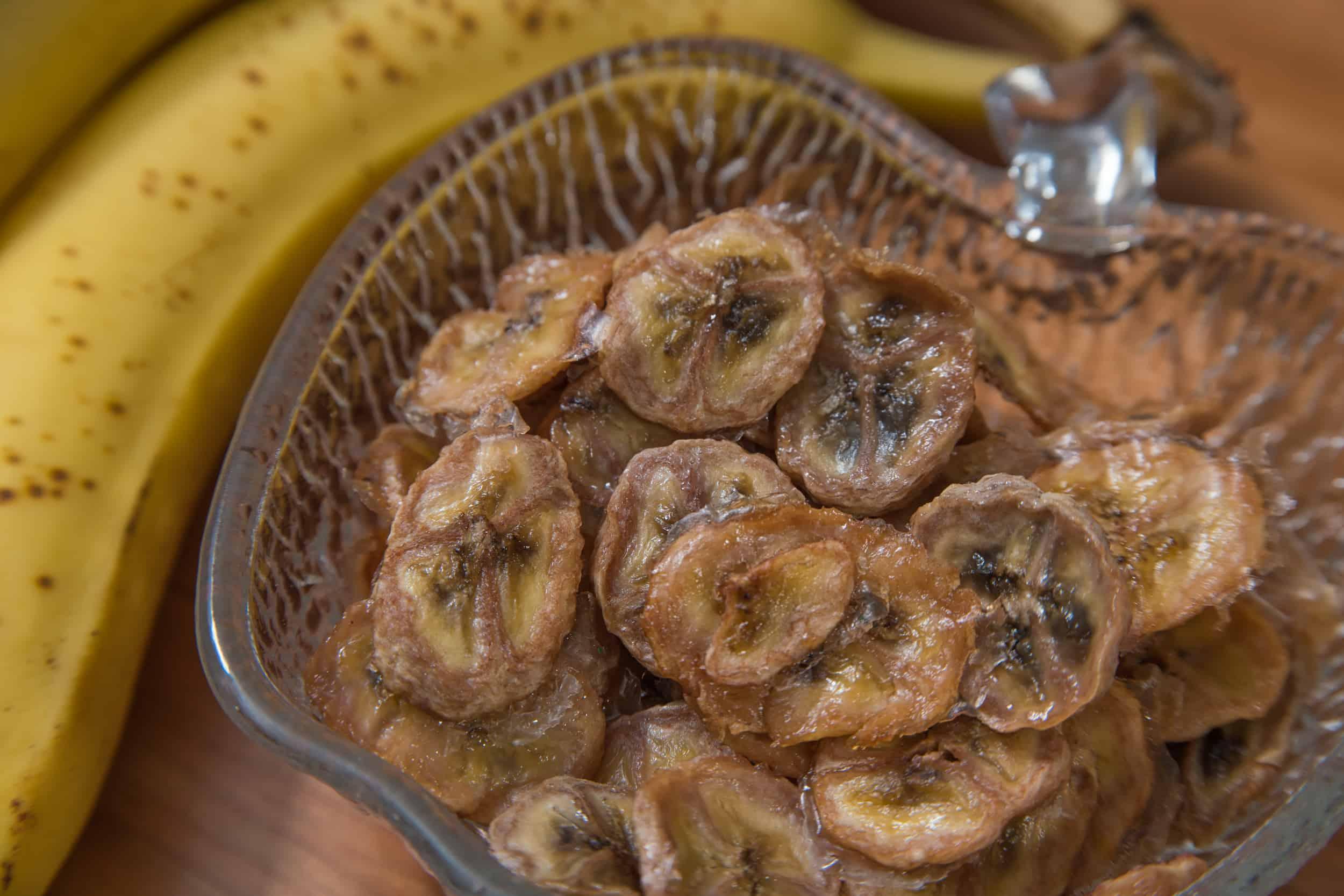 Selbstgemachte Bananenchips in einer Schüssel mit einer Banane