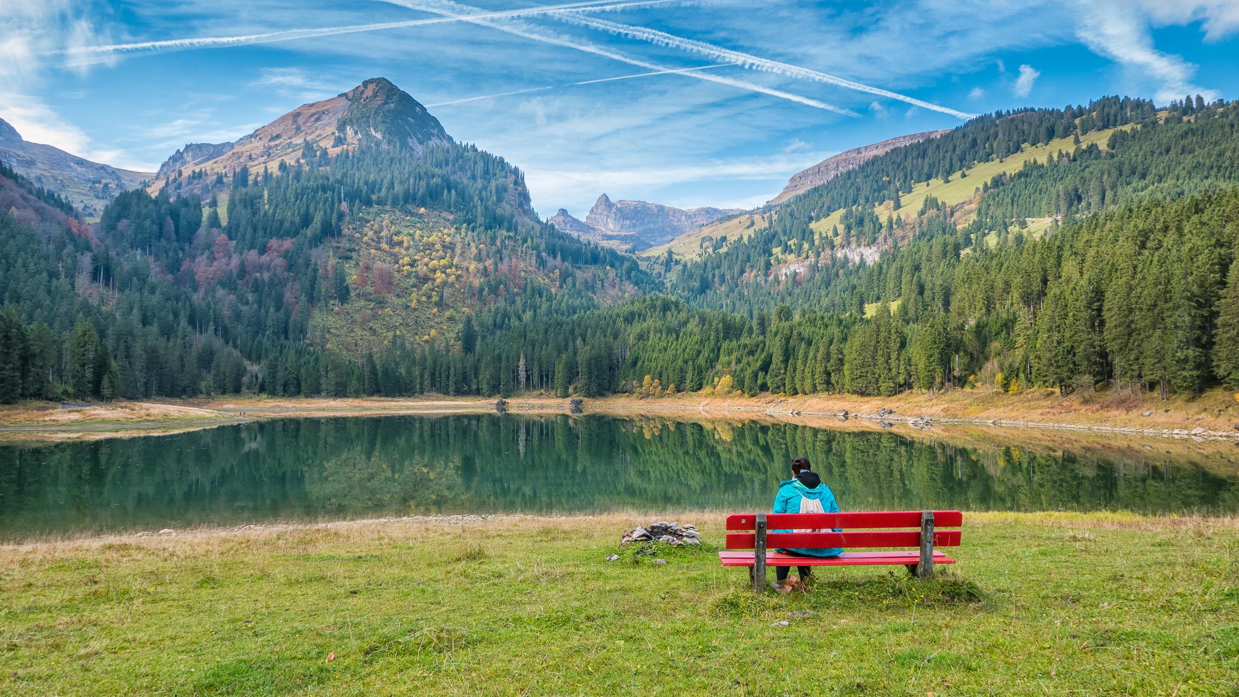 Der Voralpsee mit Bergen im Hintergrund und Lia auf einer Bank