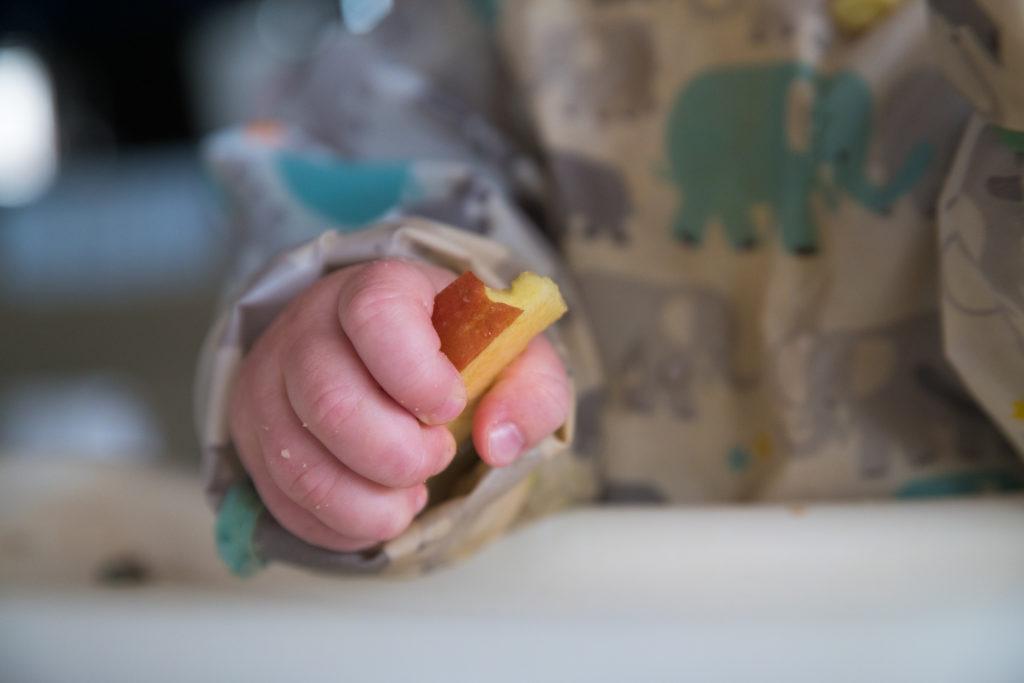 Ein Baby mit einem Stück Apfel in der Hand